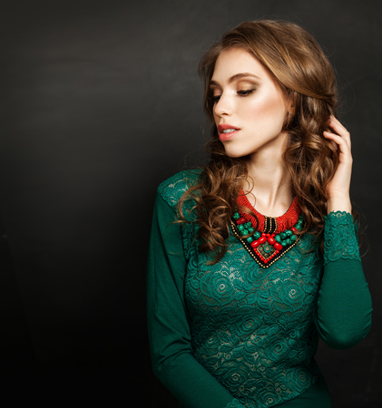 Young Perfect Woman Wearing Green Dress and Red Corals Necklace on Black Background with Copy space