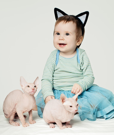 Cute little baby girl with hairless kittens