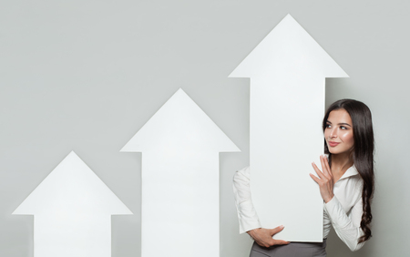 Shares Up, Business Success and Profit Concept. Smiling Business Woman with White Empty Rising Arrows