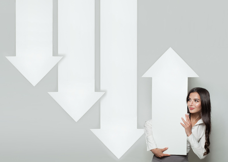 Shares Up, Business Success and Profit Concept. Brunette Business Woman with White Empty Rising Arrows. Up and Down Column Stock Photo