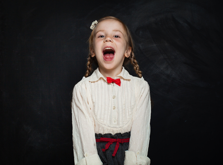 Glückliches Kindermädchen, das auf Tafelhintergrund lacht. Konzept für Kreativität und Bildung von Kindern Standard-Bild