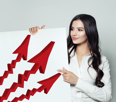 Business Woman Showing Singboard Banner with Red Rising Arrow , Representing Business Growth. Business Success and Shares Up Concept Stock Photo
