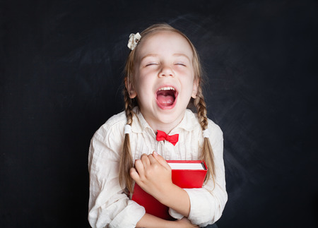 Child with book having fun and laughing. Smart child. Love school and education concept Imagens