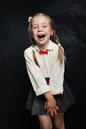 Glückliches Kindermädchen in der Schuluniform, die Spaß hat und auf Kreidetafelhintergrund lacht. Back to School Verkaufskonzept