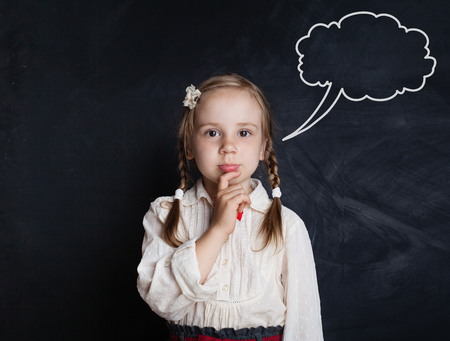Thinking little girl against speech clouds chalk drawing on blackboard background. Cute pensive child portrait