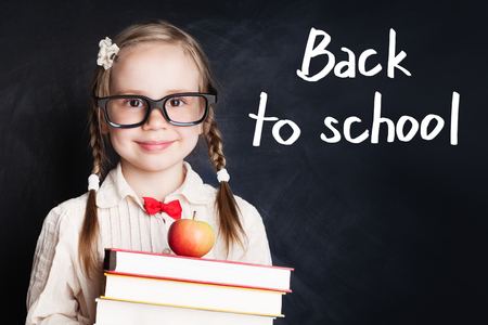 Smiling child girl in school uniform holding books and apple against chalk board background. Back to school concept Stock Photo
