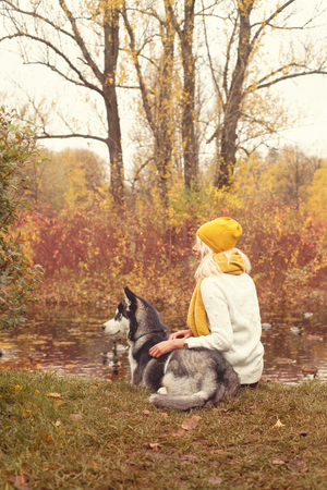Woman and dog husky outdoor in the autumn park Stok Fotoğraf