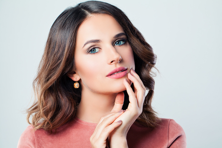 Gentle woman brunette with makeup, wavy hairstyle and manicured hand. Girl in pink clothes