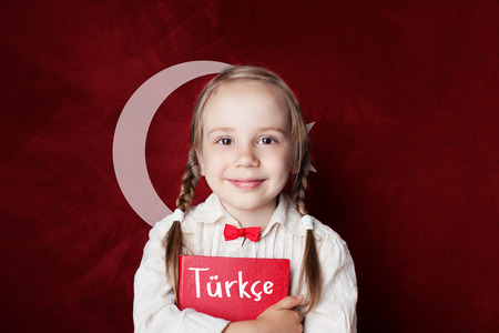 Turkish language concept. Cute child girl student on the Turkey flag background. Learn turkish language 版權商用圖片