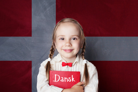 Danish concept. Child girl student with book against the Danish flag background. Learn language Banque d'images
