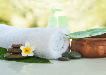 Tropical flowers, bowl of water, towel and cream tube. Body care and spa concept outdoors