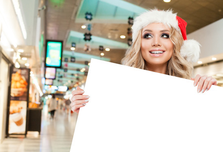 Happy Christmas woman in Santa hat showing white empty paper signboard banner with copy space on shopping mall background. Sale and offer concept Archivio Fotografico
