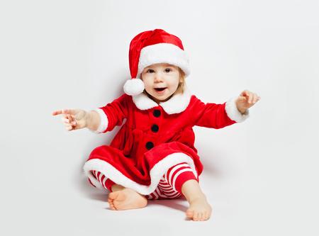 Happy child girl in Santa hat having fun on white background