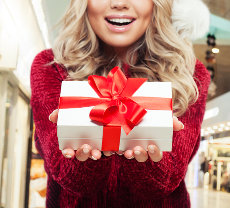 Christmas gift in female hands on shopping mall background Фото со стока