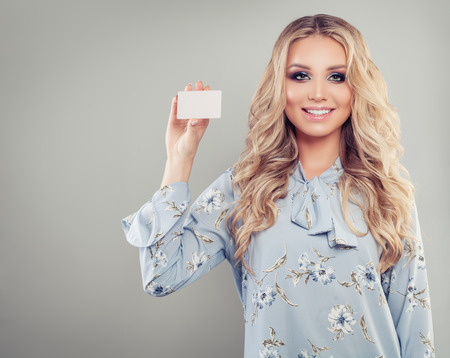 Happy successful woman holding credit card on banner background