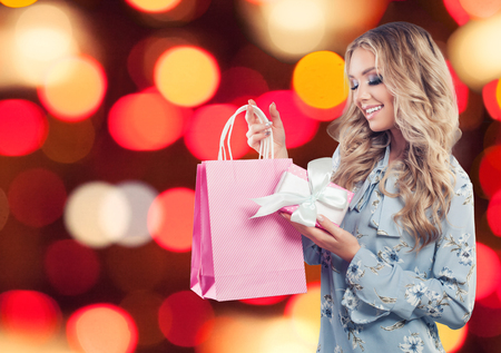 Smiling woman with pink shopping bag on celebration sparkle background