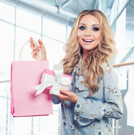 Pretty woman and pink gift and shopping bag on business background Фото со стока