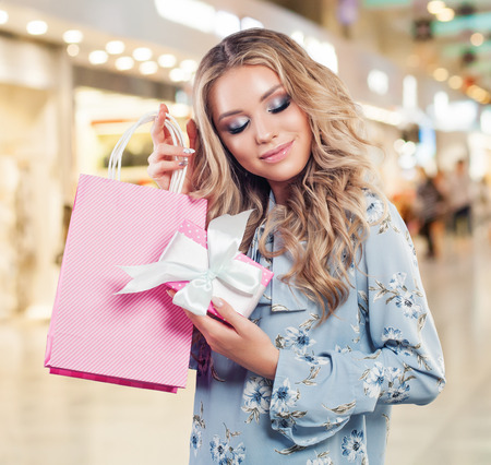 Cheerful woman with shopping bags and gift walking in shopping mall