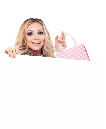 Cheerful woman smiling and holdind shopping bags and white empty paper signboard banner isolated on white background Foto de archivo