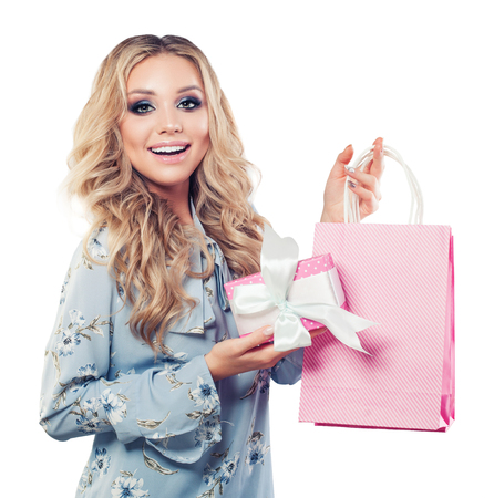 Smiling woman holding pink gift box and shopping bag isolated on white background Stock Photo