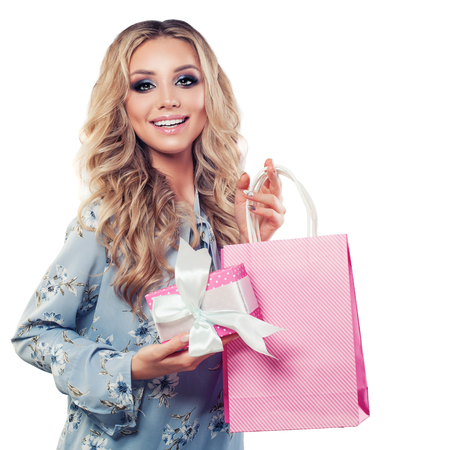 Perfect blonde woman holding gift and shopping bags isolated on white background Stock Photo