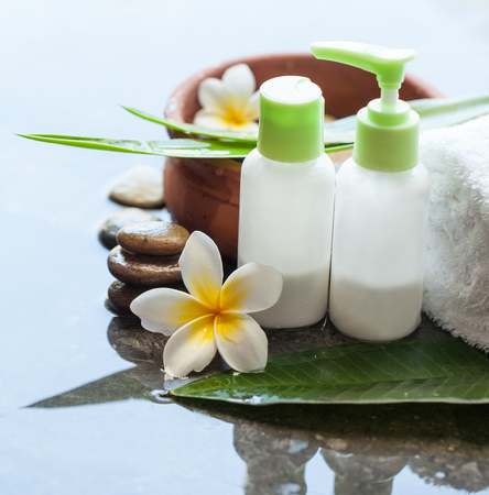 Spa Cream tubes with tropical flowers, bowl of water, towel and stones.  Body care and spa concept 免版税图像