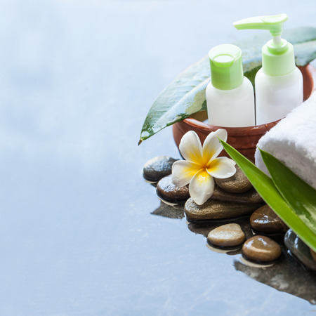 Bottles with leaves in  bowl of water, towel, flower. Body care and spa concept