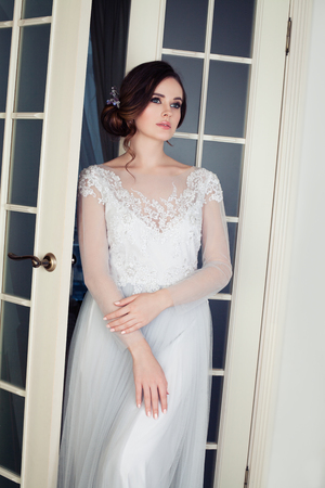 Elegant woman with makeup and bridal hair in white dress