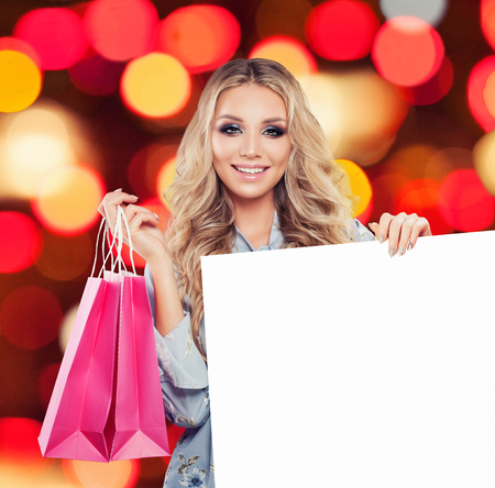 Fashionable woman with pink shopping bag and white paper board with copy space