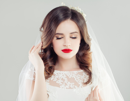 Beautiful bride woman with red lips makeup, bridal hair and white veil