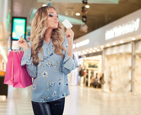 Happy model woman with empty credit card and and shopping bags in shopping mall