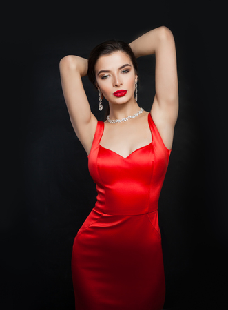 Perfect brunette woman in red sexy dress. Fashion model with red lips makeup on black background