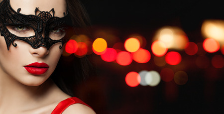 Closeup portrait of attractive woman face in black carnival mask and red lips makeup on black background with red bokeh sparkle