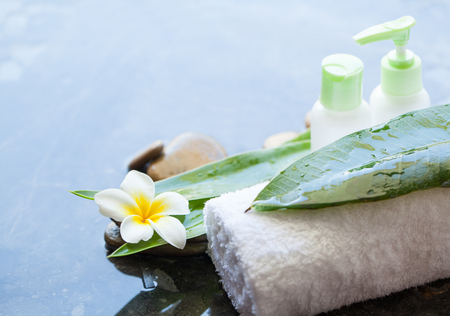 stones, towel, bottles, leaves for massage treatment on dark background with copy space.