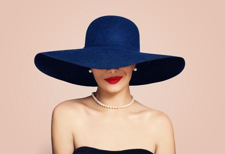 Hermosa mujer sonriente con sombrero elegante sobre fondo rosa. Chica elegante con maquillaje de labios rojos, retrato de moda Foto de archivo
