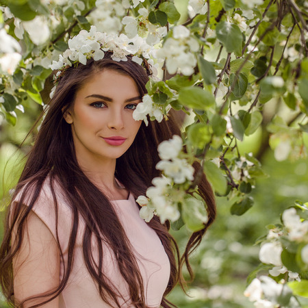 Young woman in flowers outdoors. Perfect female model in blossom garden