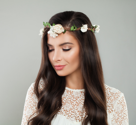 Young beautiful woman with white flowers on head, natural makeup and long healthy hair portrait