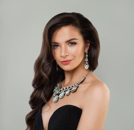 Kobieta biżuteria. Idealna kobieta z makijażem, kręconymi brązowymi włosami i diamentowym naszyjnikiem