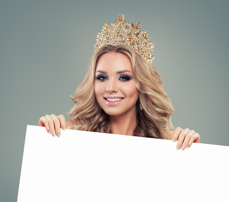 Beautiful happy woman in gold crown showing white empty paper board background with copy space for text, advertising marketing and product placement