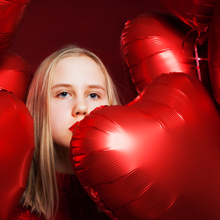 Young teen girl looking on red heart balloons background