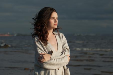 Brunette girl walking along the coastline of the sea, romantic woman portrait Banco de Imagens