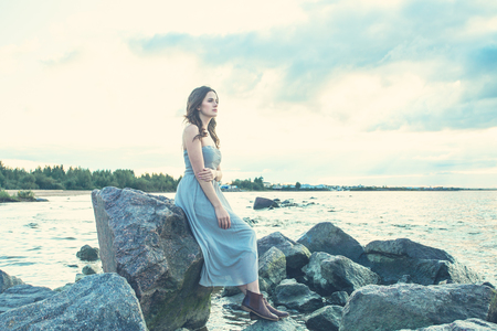 Fashion woman sitting on the coastline
