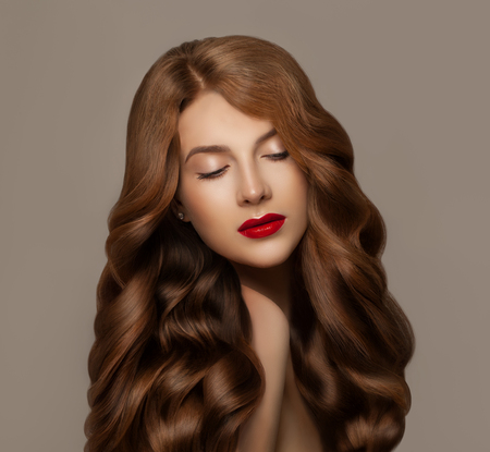Elegant young redhead woman with long ginger healthy curly hair. Haircare concept