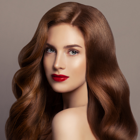 Beautiful hair woman. Female model girl with long red curly hair. Redhead woman portrait