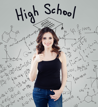 Happy student girl showing thumb up on science background. Education, high school and learning concept