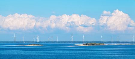 Wind farm nature background with wind turbine, blue sky and sea. Wind turbine landscape