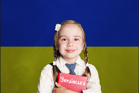 Ukraine concept with kid little girl student with red book on the Ukraine flag background. Learn ukrainian language