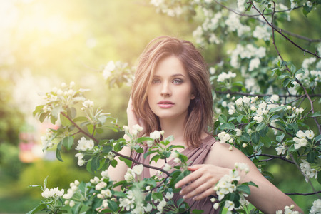 Lifestyle portrait of beautiful girl in spring blossom garden. Beauty woman on apple flowers and green leaves background