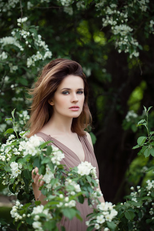 Young beautiful model woman in spring park outdoor. Elegant girl portrait