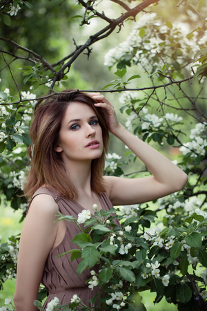 Beautiful woman in spring blossoms garden. Girl on apple flowers background outdoors